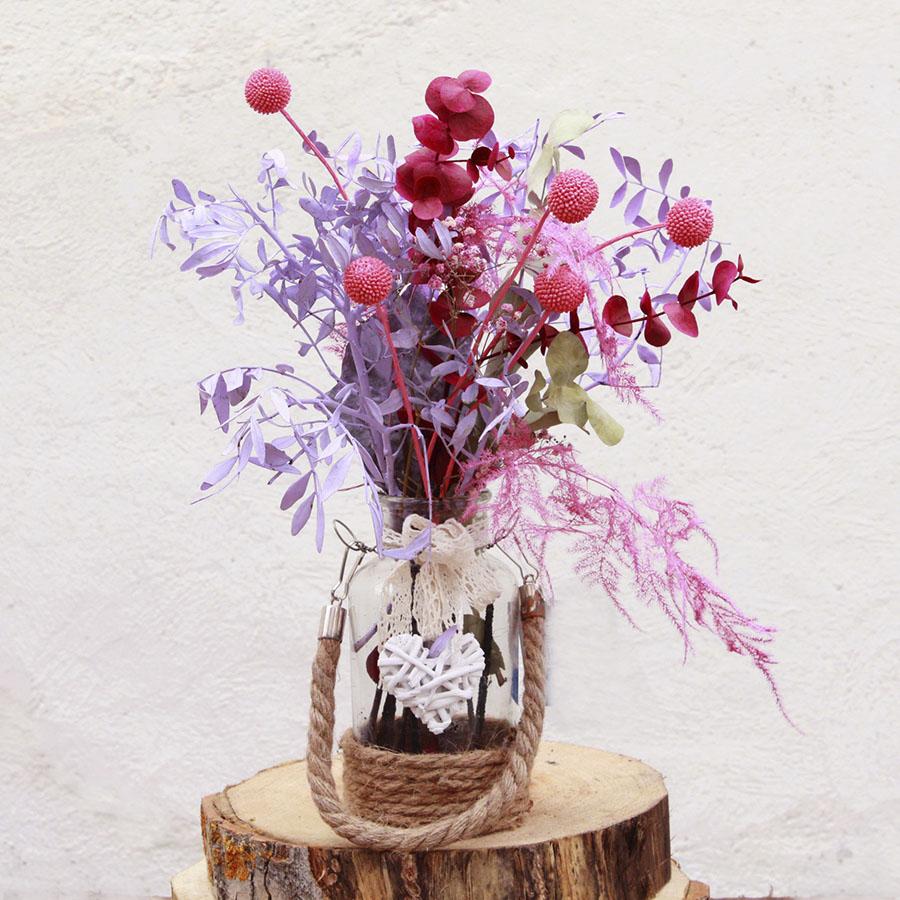 Botella de cristal con flores secas. Puede cambiar envase según existencias.