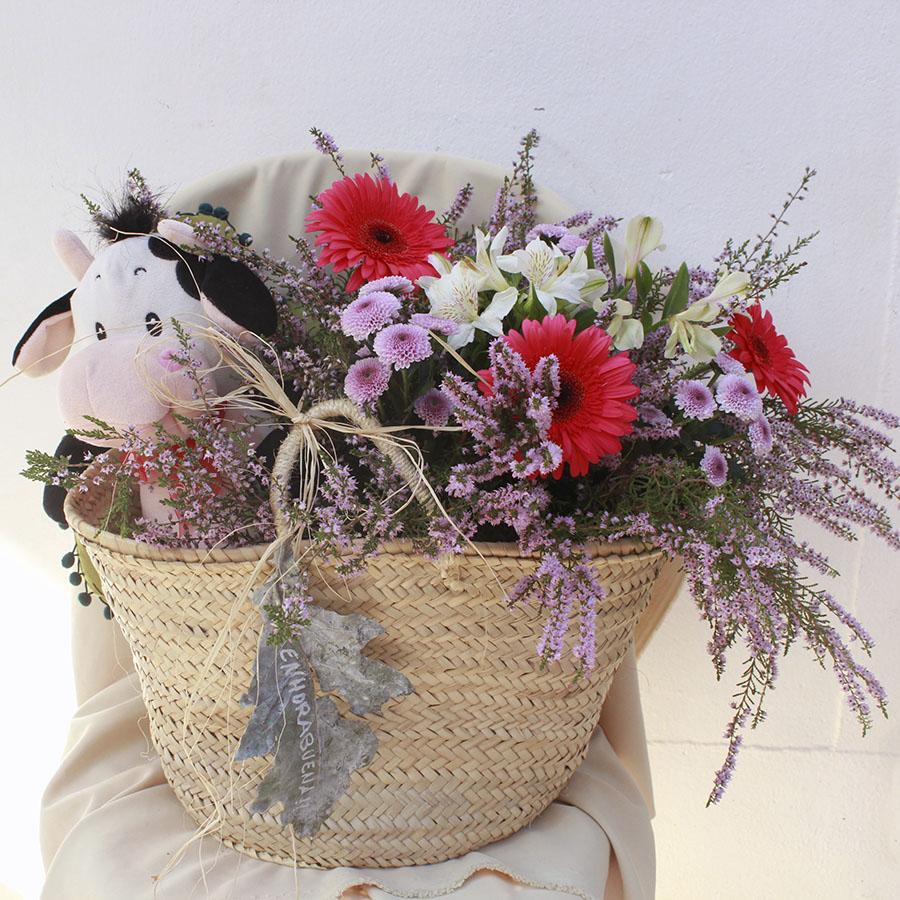 Cesta con flores y peluche bebé.