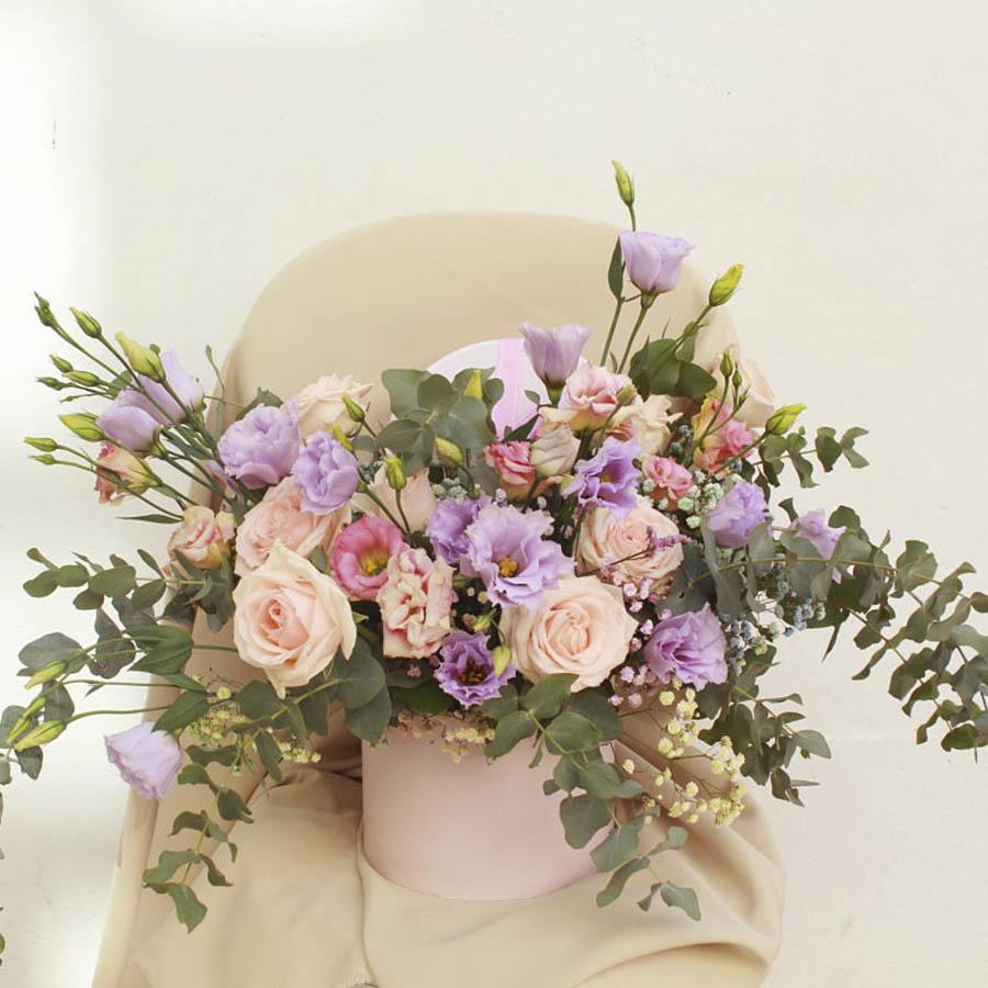 Caja sombrerera con flores variadas en tonos cálidos